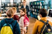 rozkošný vulkánských s batohem se usmívá na kameru při návštěvě knihovny se spolužáky