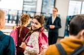 Fotografie vulkánských s batohem se usmívá na kameru při návštěvě knihovny se spolužáky