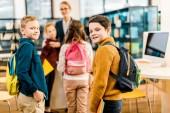 Školáci s knihami a batohy na fotoaparát v knihovně