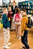 Jungen mit Büchern und Rucksäcken blicken in Bibliothek in die Kamera