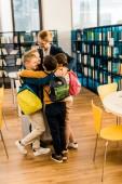 Fotografie šťastné děti s batohy objímání knihovník v knihovně
