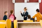 Fotografie zadní pohled na liduprázdno s batohy při pohledu na učitel dělat prezentaci na interaktivní tabule