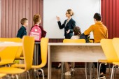 Školáci s batohy při pohledu na učitele na interaktivní tabule