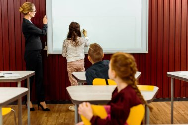 schoolkids and teacher studying with interactive whiteboard behind