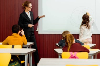 young teacher showing the whiteboard and schoolkid writing during presentation