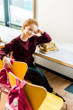 high angle view of beautiful schoolkid sitting at desk with books and smiling at camera