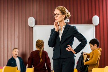 beautiful young teacher in eyeglasses looking away while schoolkids standing behind