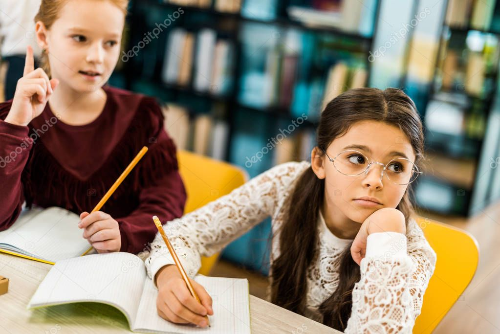 Adorable schoolgirls writing with pencils and looking away while studying in library stock vector