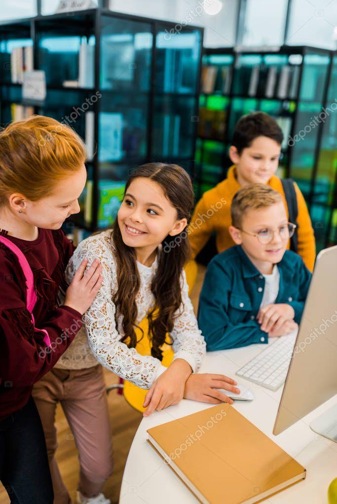 Beautiful happy schoolchildren using desktop computer together in library stock vector