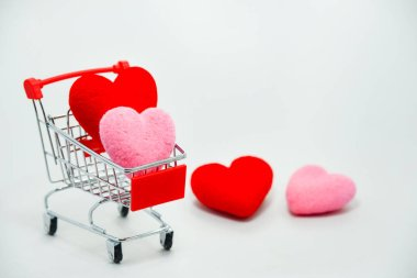 Red and Pink hearts in mini shopping cart falling on the background for valentines day. Top view and copy space.