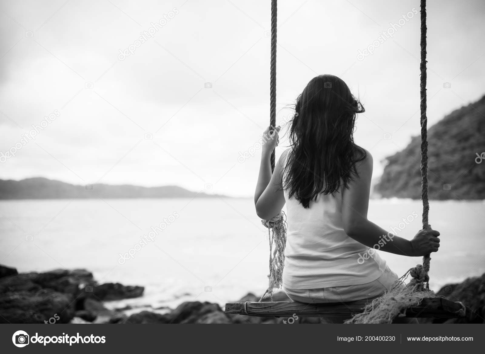 Black and white of sad and lonely woman sitting alone on a the wooden swing over the sea photo by spukkato