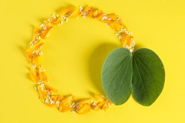 Happy Dussehra. Yellow flowers, green leaf and rice on yellow background. Dussehra Indian Festival concept.