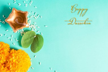 Happy Dussehra. Clay Diya lamps lit during Dussehra with yellow flowers, green leaf and rice on green pastel background. Dussehra Indian Festival concept.
