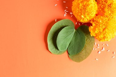 Happy Dussehra. Yellow flowers, green leaf and rice on orange background. Dussehra Indian Festival concept.