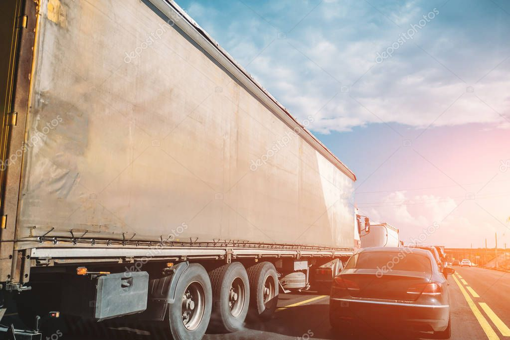 Truck transportation and cars on road or highway at sunset, logistic cargo shipping concept