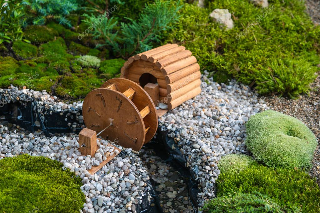 Miniature rural area or park landscape with small river and wooden water wheel among green plants, tiny toy little world concept