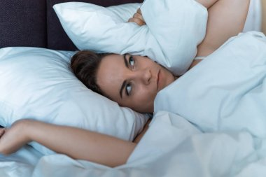 Young stressed woman cannot sleep due to noise of her neighbors from above, irritated and stressful covers her head and ears with pillow