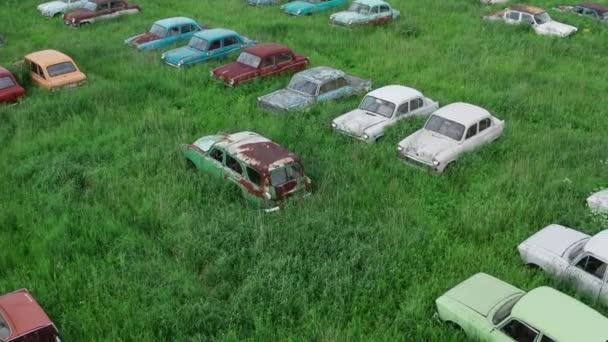Letecký pohled na mnoho starých rezavých opuštěných aut v zeleném poli, veteránů