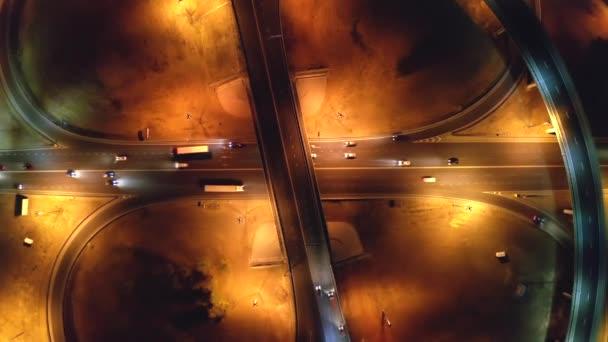 Dálniční a silniční křižovatka s mosty v nočním městě, letecký pohled shora z dronu, automobilová doprava, doprava a urbanistický development koncept