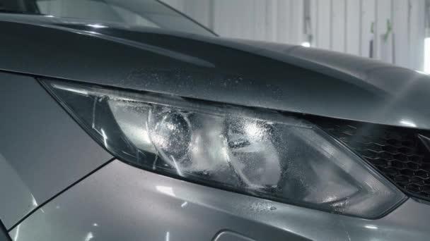 Pracovník rozstřikuje čisticí prostředky na reflektor auta a otírá mikrovlákny, připravuje reflektor pro leštění. Detailní koncepce auta