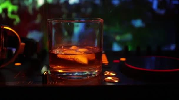 Üveg whisky, jégkocka, belül a dj kontroller, nightclub. DJ konzol club ital, zene buli, szórakozóhely, diszkó fények. Szelektív összpontosít
