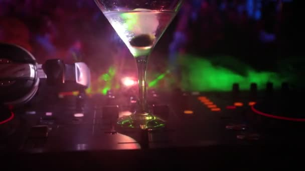 Glass with martini with olive inside on dj controller in night club. Dj Console with club drink at music party in nightclub with disco lights.