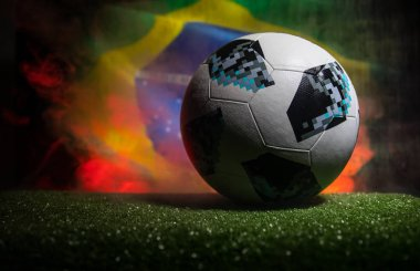 BAKU,AZERBAIJAN - JUNE 21, 2018 : Creative concept. Official Russia 2018 World Cup football ball The Adidas Telstar 18 on dark toned foggy background with flag of Brazil. Selective focus