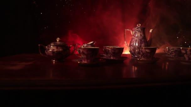 Koncepční téma, kávu nebo čajový obřad. Staré vintage keramické čajové nebo kávové konvice s poháry džbán a cukru cup na tmavém tónovaný pozadí se světlem a kouř. Prázdné místo textu. Jezdec výstřel