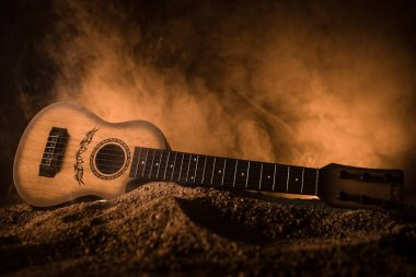 Music concept. Acoustic guitar isolated on a dark background under beam of light with smoke with copy space. Guitar Strings, close up. Selective focus.