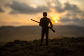 Silhouette von Militärsoldat oder Offizier mit Waffen bei Sonnenuntergang. Schuss, halten Pistole, bunten Himmel, Berg, Hintergrund. Dekoration mit Spielzeug Soldat