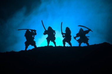 Silhouette of samurais with swords. Picture with four samurais and sunset sky. Selective focus