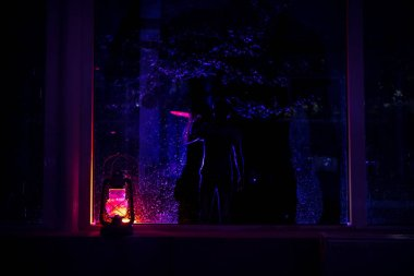 Horror Halloween concept. Burning old oil lamp standing on window with silhouette of an unknown shadow figure with backlight. Night scenery of a nightmare scene. Selective focus.
