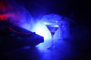 Glass with martini with olive inside on dj controller in night club. Dj Console with club drink at music party in nightclub with stylish oriental shisha