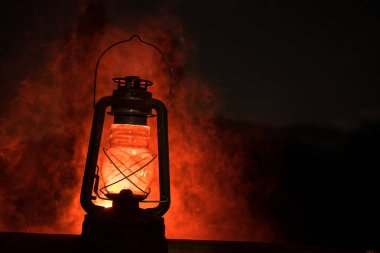 Horror Halloween concept. Burning old oil lamp in forest at night. Night scenery of a nightmare scene. Selective focus.