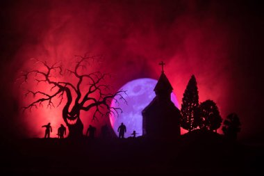 Scary view of zombies at cemetery dead tree, moon, church and spooky cloudy sky with fog, Horror Halloween concept. Toned