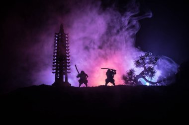 Samurai fighting concept. Silhouette of samurais in duel near tree and old temple. Table decoration with dark toned foggy background. Selective focus