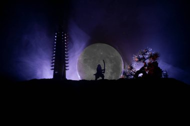 Samurai fighting concept. Silhouette of samurai with sword near tree and old temple. Table decoration with dark toned foggy background. Selective focus