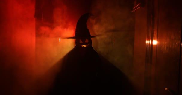 Koncept Halloween. Strašidelné silueta v temné chodbě s dýňová hlava. Tónovaný světlo s mlhou na pozadí.