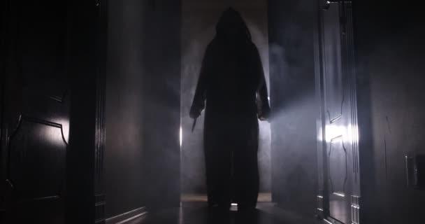 Strašidelné silueta v temné opuštěné budovy. Horor Halloween koncept. Temné chodby s silueta hrůzy osoby stojící v centru. Tónovaný světlo a mlha na pozadí.