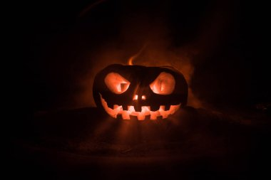 Halloween pumpkin smile and scrary eyes for party night. Close up view of scary Halloween pumpkin with eyes glowing inside at black background. Selective focus stock vector