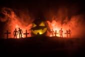 Fotografie Beängstigend Blick auf Zombies am Friedhof toter Baum, Mond, Kirche und gruselige Bewölkter Himmel mit Nebel, Horror Halloween-Konzept mit glühenden Kürbis. Selektiven Fokus