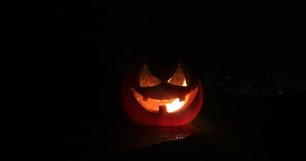 Horror Halloween koncepció. Közelkép ijesztő halott Halloween tök világít a sötét háttérben. Rohadt tökfej. Szelektív fókusz