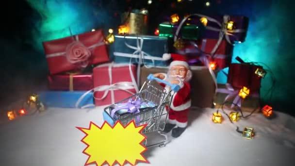 Nový rok nebo vánoční dovolená nákupy koncept. Uložení akcí. Santa Claus přepravní vozík vozík na sněhu. Zásobník dárkových krabiček na pozadí. Prázdné místo na štítku pro váš text