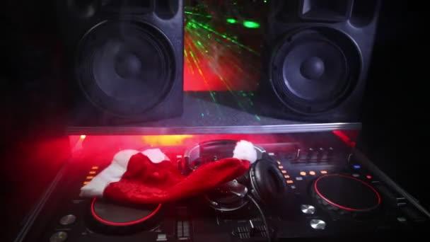 DJ mixer s sluchátka na pozadí temné noční klub s Evou nový rok vánoční stromeček. Detailní zobrazení prvků nového roku na stole Dj. Holiday party koncept. Prázdné místo
