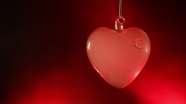 Valentines Day Concept. Glass transparent heart on dark, glass heart glows, glass painting, black background. Emptry space for your text