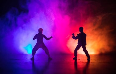Karate athletes fighting scene.Character karate. Posing figure artwork decoration. Sports Scramble or Man practicing karate on decorated foggy background with light.