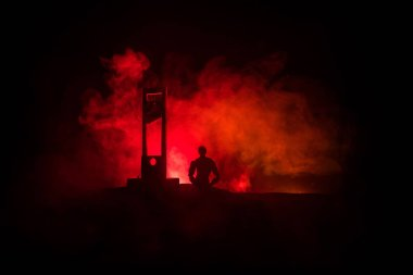 Horror view of Guillotine. Human at guillotine on a dark foggy background. Execution concept