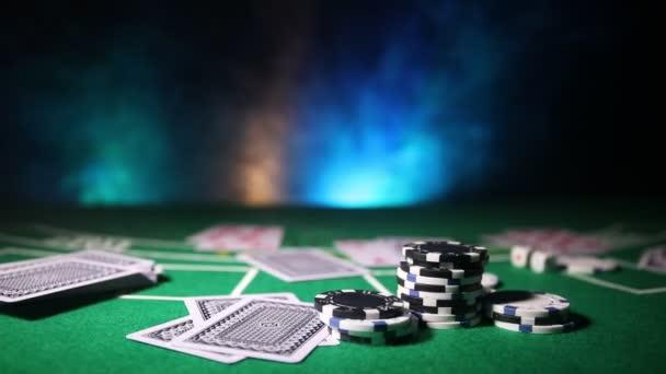Carte e fiches sul tavolo del casinò di feltro verde. Astratto sfondo con lo spazio della copia. Tema di giochi dazzardo, poker, casinò e carte. Elementi del casinò su verde. Messa a fuoco selettiva
