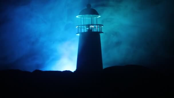 Artwork decoration. Lighthouse with light beam at night with fog. Old lighthouse standing on mountain. Table decoration. Toned background. Moonlighting. Selective focus