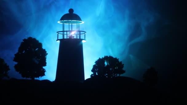 Kunstwerk Dekoration. Leuchtturm mit Lichtkegel bei Nacht mit Nebel. alter Leuchtturm auf dem Berg. Tischdekoration. getönten Hintergrund. Schwarzarbeit. Selektiver Fokus